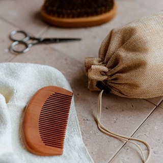 a wooden comb, brush, manicure scissors, a small towel, and a drawstring bag on a cream-colored tile surface