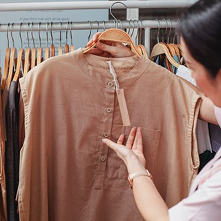 a person clothes shopping, inspecting a high-quality tan shirt
