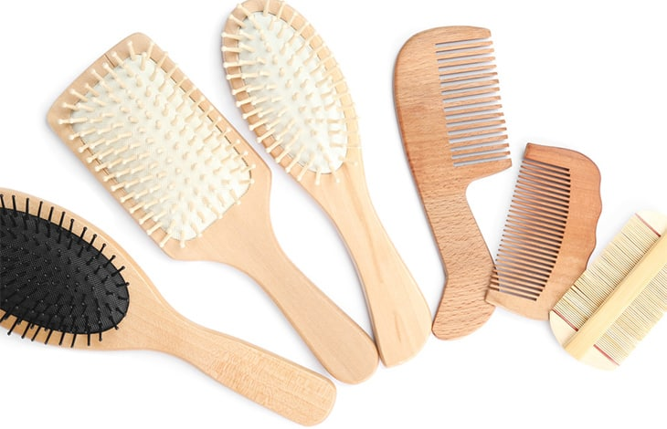 wood hair brushes and combs lined up in an arc from largest to smallest