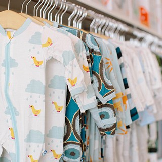 a row of patterned baby clothes with zippers hanging on wooden hangers in a shop