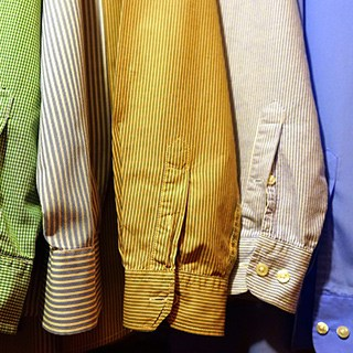 a row of dress shirt sleeves of various colors