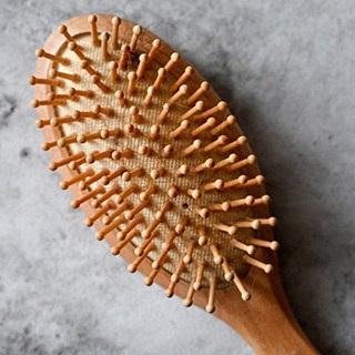 A wooden paddle hairbrush, facing up