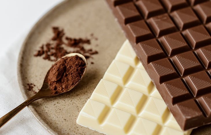 a spoonful of cocoa powder and bars of chocolate and white chocolate on a plate