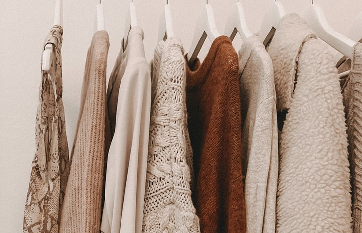 High-quality sweaters in various beige and brown colors handing on white wooden hangers