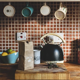 wood kitchen counter with red tile backsplash, a black teapot, and hanging mugs