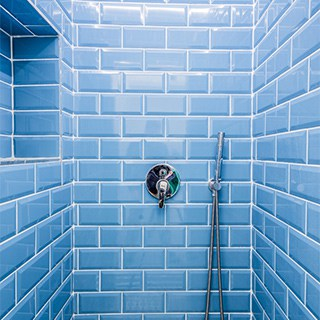 shower tiled with light blue tile and white grout