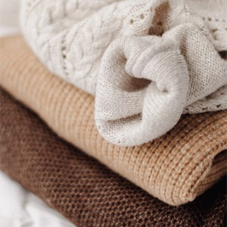 stack of brown, tan, and cream folded sweaters