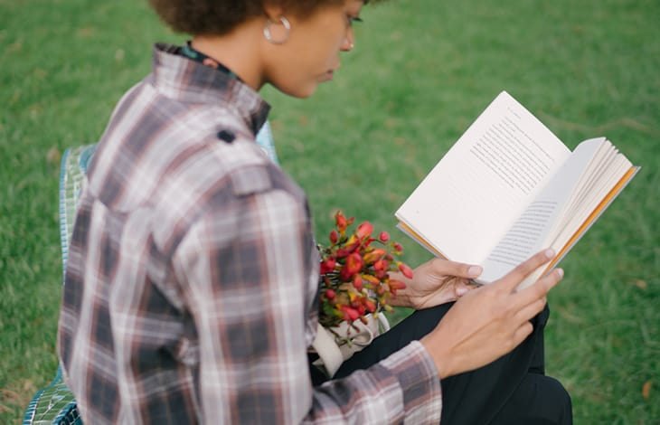 a person in a plaid shirt sitting outside reading a book