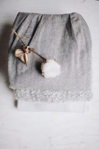 a raw cotton flower on top of a stack of folded gray and white cotton fabrics