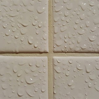 closeup of wet, white tile covered in water droplets