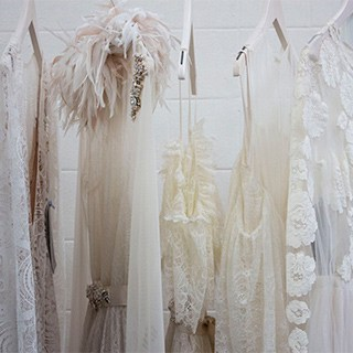 hand wash only, delicate white clothing made of sheer and lace fabrics hanging on white wooden hangers