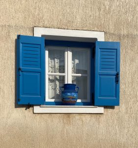 a blue vase sitting in the middle of a clean glass window with white trim and blue shutters in natural light
