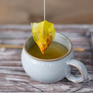 a yellow teabag lifting out of a rounded white mug filled with tea