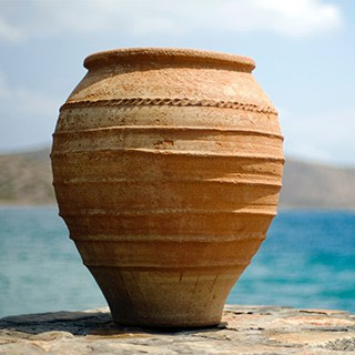 ribbed, rounded terra cotta pot sitting  outside on a stone surface in front of water and a blue sky