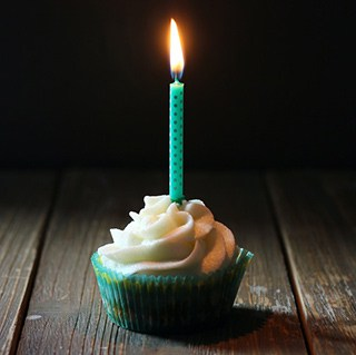 a teal-colored cupcake with white frosting and a lit teal, dotted birthday candle on a wood table against a dark background