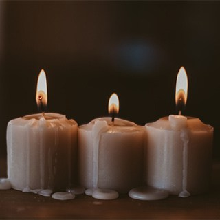 three small, cream-colored pillar candles burning and dripping wax