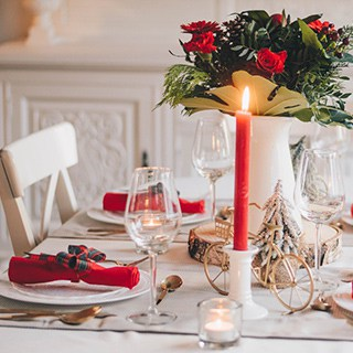red taper candle on white table with white dishes and red napkins and a centerpiece of red roses