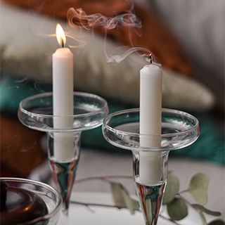 two small white taper candles in holders with clear glass drip dishes