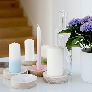different types and colors of candles on a white table beside purple flowers in white vases