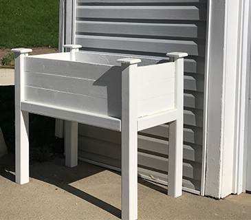 a photo of a raised, white, wood planter in front of a gray building