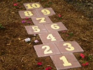 hopscotch board made of numbered square bricks on a grass lawn