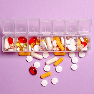 pills of various shapes and colors stored in a clear plastic medication storage container