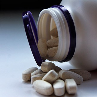 white speckled medication tablets spilling out of a white storage bottle with a dark blue lid.