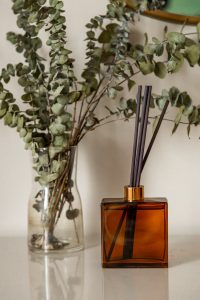 Black reed essential oil diffusers placed in a square amber jar beside a clear glass vase of natural eucalyptus