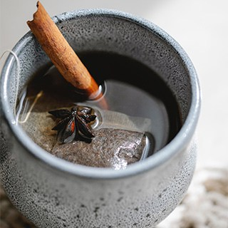 a brewing teabag and cinnamon stick in a blue/gray mug filled with black tea