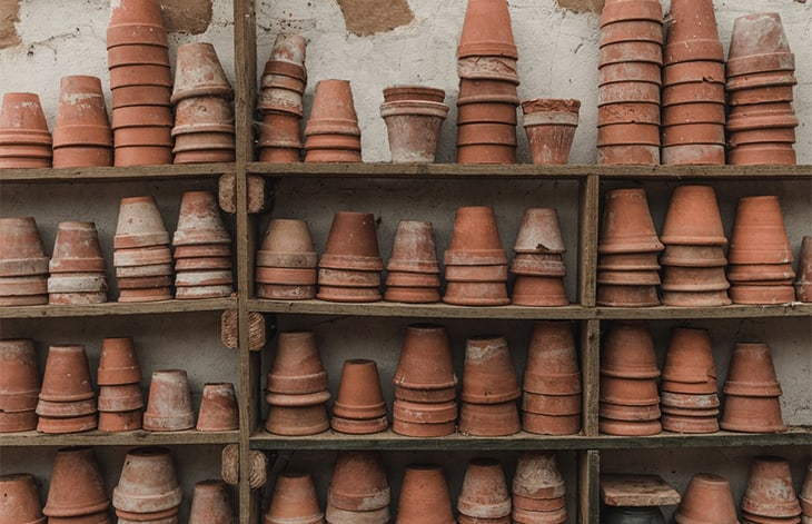 worn terra cotta pots stacked on wooden shelves against a white wall