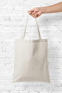 a hand holding a canvas tote bag in front of a white brick wall