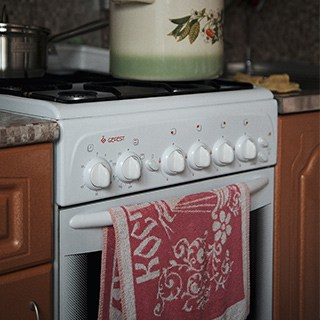 a white oven with a red and white kitchen towel draped over the handle