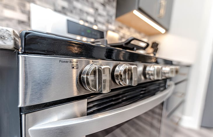 closeup of the knobs on a silver and black oven range