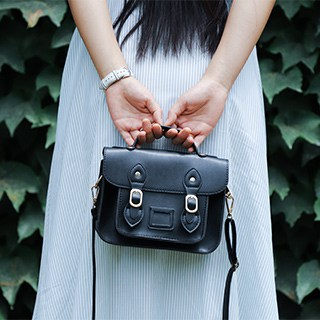 a person with long dark hair in a white dress holds a black purse behind their back with both hangs