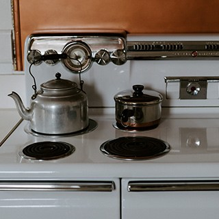 metal teapot and sauce pan siting on a white stovetop