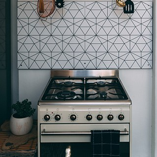 an older oven with grill stove against a wall