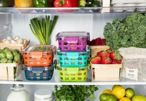 shelves of a fridge filled with colorful storage containers and various types of produce