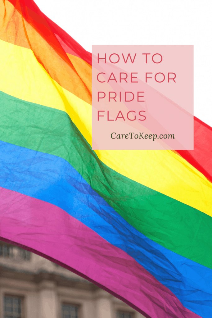 A rainbow pride flag blowing in the wind in behind a pink box with dark pink and dark green writing that reads: How to care for pride flags; CareToKeep.com