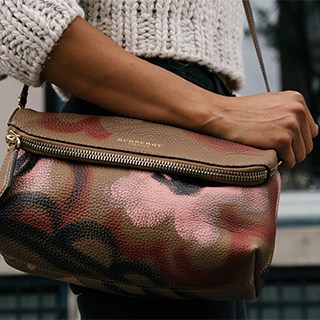 a person clutching a folded brown, pink, and black purse hanging over their shoulder