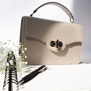 a beige handbag wits beside a notebook, black pen, and sprig of baby's-breath