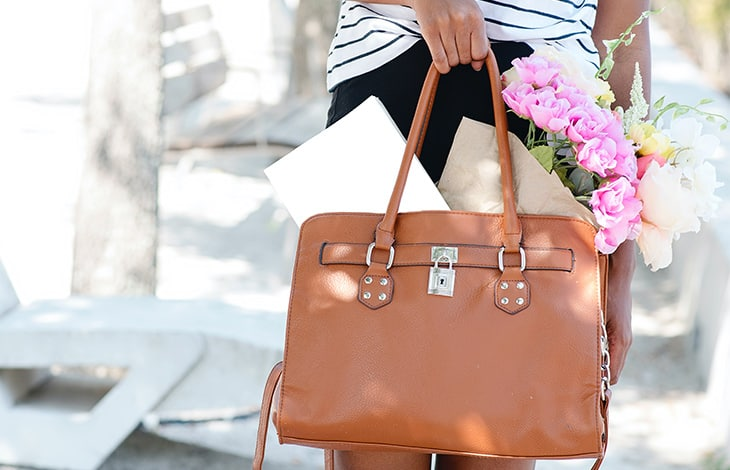 a hand carries a brown purse filled with a white box and pink flowers
