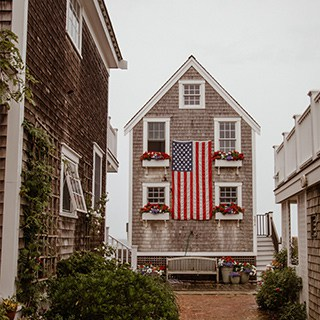a tall brick house with white windows, flower-filled window boxes, and a large American flag on the front of the house.