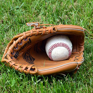 a baseball glove with a baseball in it lying on the grass