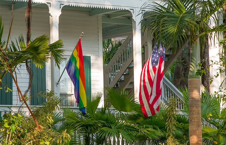 a rainbow pride flag and an American flag hang from a white house's banisters