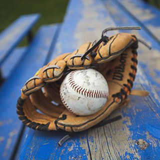 a baseball glove and baseball on a wood bench with chipped blue paint