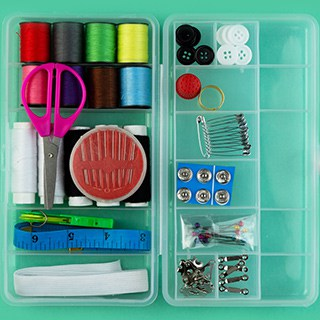 sewing kit sorted into a plastic container with compartments
