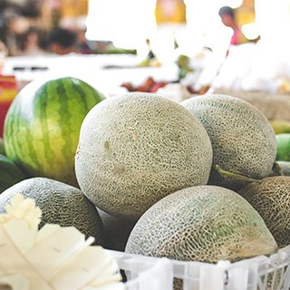 whole melons in a basket at a grocery store