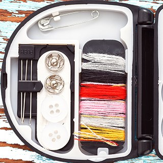 an open soewing kit with thread, buttons, needles, and a safety pin