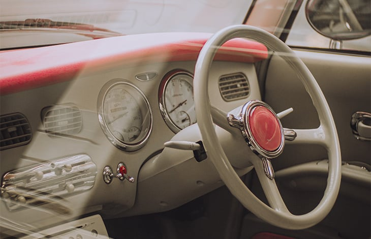 a pink and gray car dashboard and wheel