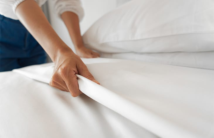 a person's hands making a bed with crisp white sheets